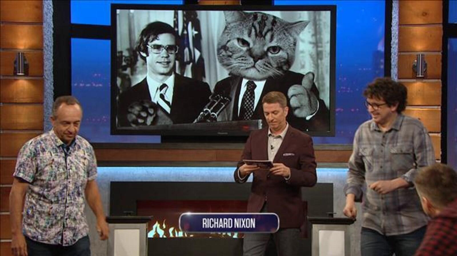 Deux participants essaie de deviner qui est caché derrière une grosse face de chat.