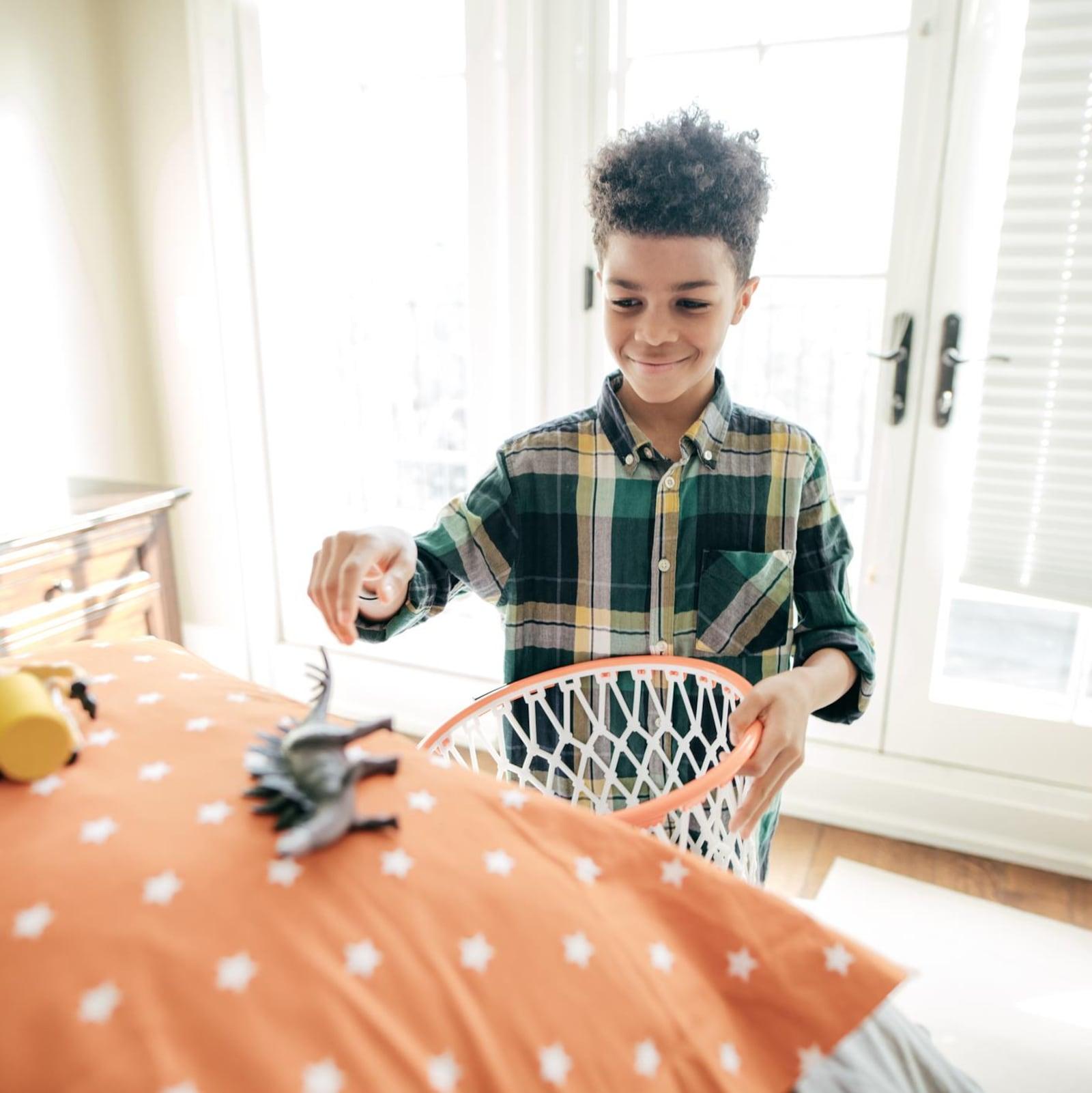 Un petit garçon ramasse des jouets sur son lit.
