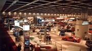 Un jeu de piste de course géant, plusieurs modèles d'autos, surtout dans les tons de rouge orangé, un tapis beige épais couvre le sol.