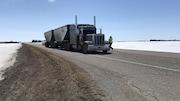 Un camion semi-remorque est stationné sur une route bordée de champs enneigés.