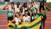Des membres de l'équipe d'athlétisme de la Saskatchewan montrent fièrement leurs médailles en tenant le drapeau fransaskois.