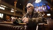 Agenouillé sur un banc d'église, un homme portant des lunettes fumées tient dans ses mains un chapelet multicolore.