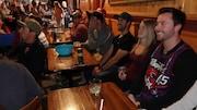 Des gens assis à des tables dans un bar et qui regardent un écran.