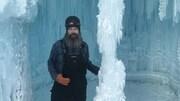 L'artiste debout à côté d'une colonne de glace en habit de neige.