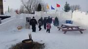 Des hommes et leurs enfants franchissent un trou à travers de château de neige.