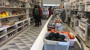 Une boutique longue et étroite avec des clients devant des étagères.