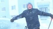 Un homme sourit en maniant une pelle dans la neige devant un édifice à logements.