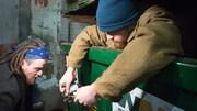 Alexandre, debout dans le conteneur, remet des objets à son frère.