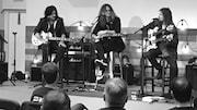Trois guitaristes sont sur une scène, assis sur des hauts tabourets, leurs guitares avec eux. Ils parlent dans des micros, à des gens assis dans la salle.