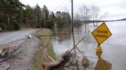 Une pancarte annonçant une traverse de bernaches et de canards est en partie enfoncée dans des eaux d'inondation.