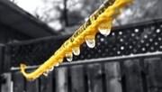 Des gouttes d'eau glacées pendent d'une corde jaune.