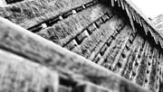 Une photo en noir et blanc de glaçons qui pendent sous le rebord d'une toiture.