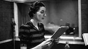 Dans un studio de radio et texte en main, la comédienne Judith Jasmin.