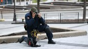 Le policier a un genou au sol. Il a enlevé son casque de protection le temps d'ajuster son masque à gaz et d'en vérifier l'étanchéité.