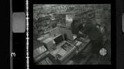 Image de caméra de surveillance où l'on voit deux personnes enlacées par dessus un comptoir-caisse dans un dépanneur.