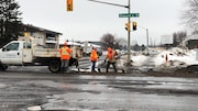 Trois hommes équipés de pelles derrière une camionnette au milieu d'une intersection.