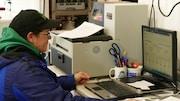 Une femme assise devant un ordinateur dans un bureau encombré, regarde avec inquiétude des prévisions météo qui annoncent du mauvais temps.