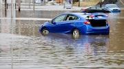 Une voiture bleue dans une rue inondée à Beauceville