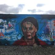 Une murale colorée à l'effigie d'une jeune fille portant la mention «Arrêtez les mensonges. Nous sommes au pays du pétrole», en anglais.