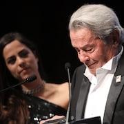 L'acteur Alain Delon, en larmes, devant un micro, après avoir reçu une Palme d'or d'honneur au Festival de Cannes. On aperçoit sa fille Anouchka derrière.
