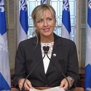 Une femme aux yeux bleus et aux cheveux blonds, dans le salon bleu du Parlement, à Québec