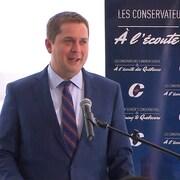 Andrew Scheer, en conférence de presse. « À l'écoute des Québécois », peut-on lire sur une pancarte installée à ses côtés.