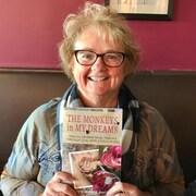 Une femme souriante aux cheveux courts est assise et tient dans ses mains un livre