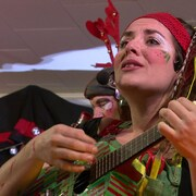 Une image rapprochée du visage d'Ariane DesLions qui joue de son ukulele en chantant.