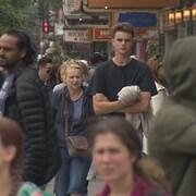 Des gens marchent sur un trottoir à proximité de commerces.