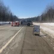 Une voiture de la Sûreté du Québec et des cônes bloquent une route rurale l'hiver.