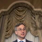 Un homme portant des lunettes parle sur une scène.