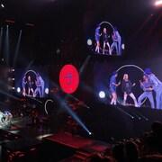 On voit le groupe sur scène avec Céline Dion et sur plusieurs écrans.