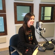 Catherine Fournier est assise devant le micro dans le studio de radio.