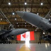 Une photo montre deux avions de chasse CF-18 des Forces armées canadiennes sont dans hangar.