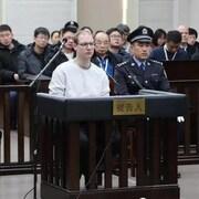 Un homme est assis dans le box des accusés flanqué de deux policiers chinois.