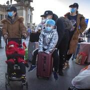 Plusieurs Chinois traînant des valises portent des masques à l'extérieur à Pékin.
