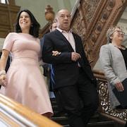 Valérie Plante, vêtue d'une robe rose, descend les marches.