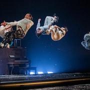 Cinq acrobates dans les airs pendant un saut.