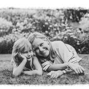 une femme et sa fille couchée dans l'herbe.