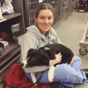 une femme assise en tailleur avec un chien sur les genoux dnas une clinique vétérinaire.
