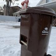 Un bac brun de compostage de la Ville de Gatineau dans la neige.