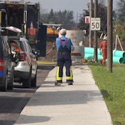 Un travailleur observe le site où des travaux d'excavation ont provoqué la fuite de gaz.