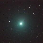 Une comète brille au centre d'un ciel étoilé.
