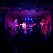 Des musiciens se produisent sur scène dans une lumière rose.