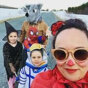Guillaume porte une tête de mascotte de loup, une de ses filles porte un costume de Spiderman, une autre est déguisée en sorcière et la plus petite, en extraterrestre.
