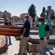 Des employés de pompes funèbres en Espagne portant des masques faciaux transportent le cercueil d'une victime de la COVID-19.