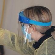 Une femme vêtue d'un sarrau, d'un masque et d'une visière.