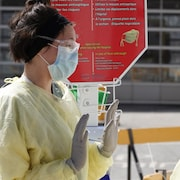 Deux femmes portant masque, sarrau et gants.