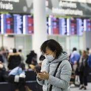 Une personne portant un masque dans l'aéroport Pearson de Toronto.
