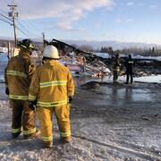 Quatre pompiers examinent les ruines